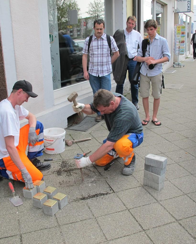 Mitarbeitern des städtischen Bauhofs leisten technische Hilfe bei der Verlegung der Stolpersteine - hier vor dem Haus Schlossstraße 2